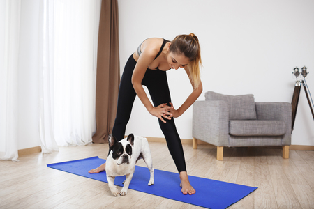 Beautiful fitness girl make sport exercises on yoga-mat with dog Archivio Fotografico