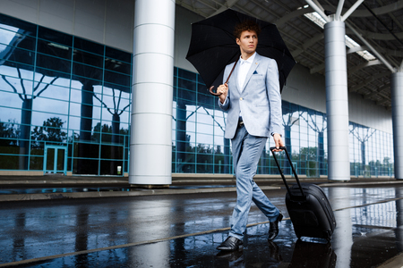 looking aside: Picture of  young redhaired businessman holding black umbrella and suitcase walking in rain looking aside