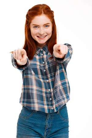 foxy girls: Portrait of young beautiful ginger girl pointing fingers and looking at camera, smiling, over white background.