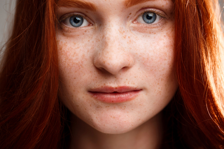 foxy girls: Close up portrait of young beautiful ginger girl looking at camera over gray background. Stock Photo