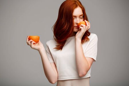 foxy girls: Portrait of young beautiful ginger girl smelling oranges, eyes closed, over gray background.