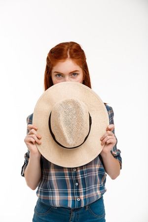foxy girls: Portrait of young beautiful ginger girl hiding face with hat, looking at camera over white background. Stock Photo