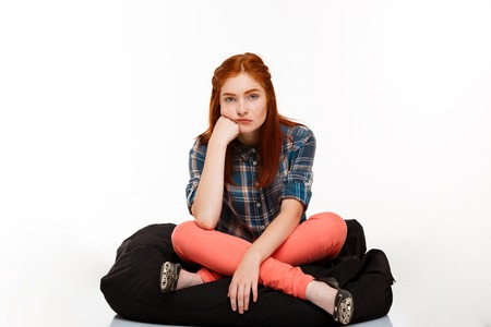 foxy girls: Portrait of young beautiful ginger girl sitting, looking at camera over white background.