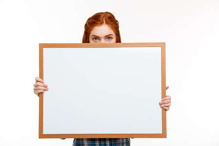 foxy girls: Portrait of young beautiful ginger girl hiding face with whiteboard, looking at camera over white background. Copy space.