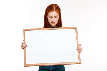 foxy girls: Portrait of young beautiful ginger girl holding whiteboard, looking at camera over white background. Copy space. Stock Photo