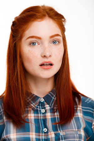foxy girls: Portrait of young beautiful ginger girl looking at camera over white background. Stock Photo
