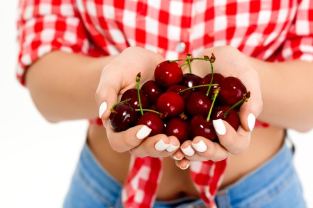 country girls: Close up photo of country girls hands holding red cherry. Stock Photo