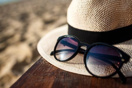 Close-up picture of hat and glasses on beach