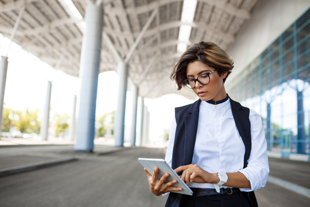 biz: Young successful businesswoman in glasses looking at tablet, standing near business centre.