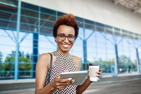 biz: Young successful african businesswoman in glasses smiling, looking at camera, holding tablet and coffee, standing near business centre. Stock Photo