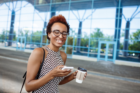 biz: Young successful african businesswoman in glasses smiling, looking at phone, holding coffee, standing near business centre.