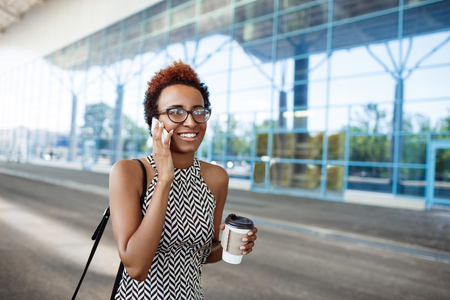 biz: Young successful african businesswoman in glasses speaking on phone, smiling over business centre. Stock Photo
