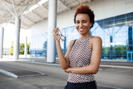 biz: Young successful african businesswoman smiling, looking at camera, holding glasses, standing near business centre.