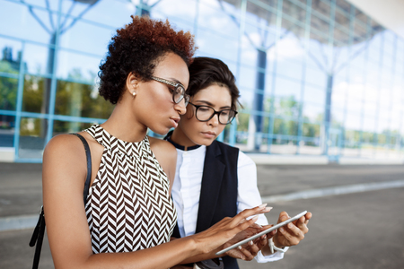 biz: Two young successful businesswomen in glasses looking at tablet, discussing over business centre. Stock Photo