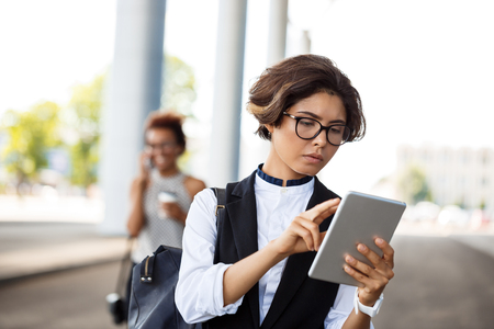 biz: Young successful businesswoman in glasses looking at tablet over business centre.