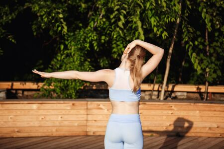 yoga outside: Young beautiful blonde girl in sport suit standing back to camera, practicing yoga outside at sunrise.