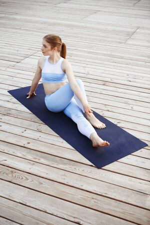 yoga outside: Young beautiful blonde girl in sport suit practicing yoga outside. Copy space.