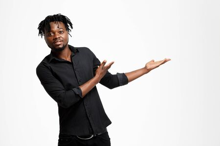Young successful african businessman in black shirt pointing hands in side, looking at camera over white background. Copy space. Stock Photo
