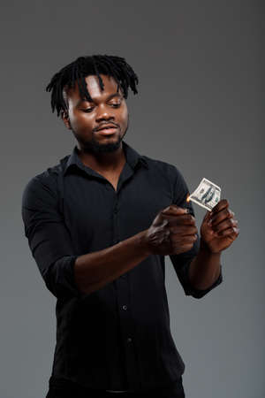 burning money: Young successful african businessman in black shirt burning money, grining over dark background.