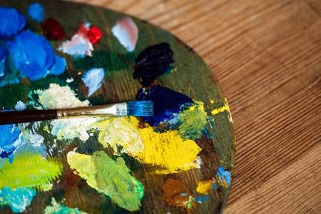 originative: Close up photo of oil paints and brush on palette over wood background. Copy space.