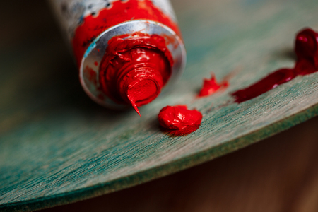 originative: Close up photo of red oil paint on palette over wood background. Copy space.