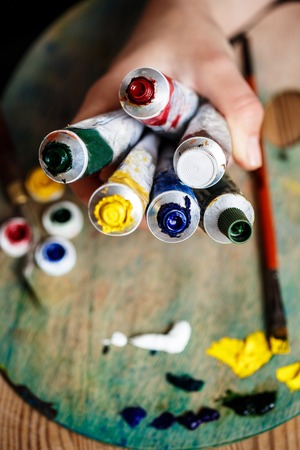 originative: Close up photo of hands holding oil paints, palette background. Stock Photo