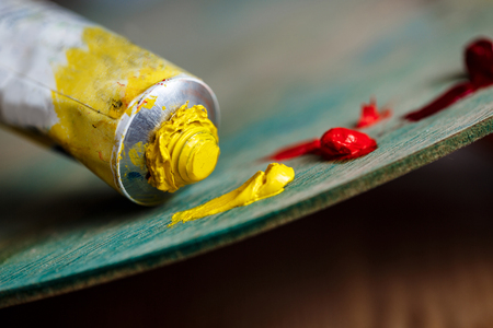 sightly: Close up photo of red and yellow oil paints on palette over wood background. Copy space. Stock Photo
