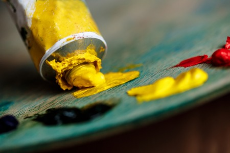 originative: Close up photo of red and yellow oil paints on palette over wood background. Copy space. Stock Photo