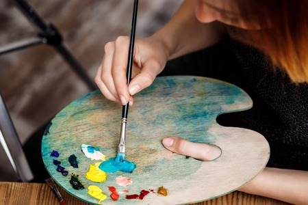 sightly: Close up photo of girl mixing oil paints on palette. Copy space.