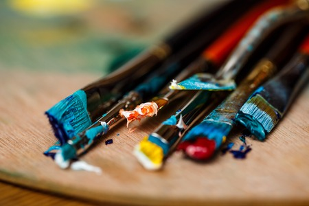 Close up photo of oil paints and brushes on palette. Copy space.