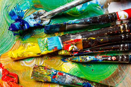 Close up photo of oil paints and brushes on palette. Copy space. From above.