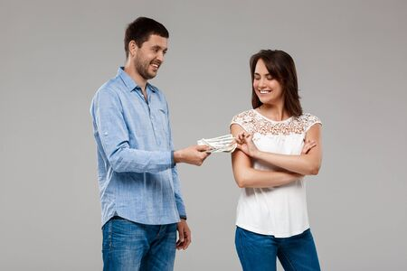 giving money: Young handsome man giving money to woman, smiling over grey background. Copy space.