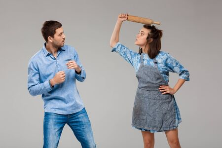 Young beautiful woman beating man with rolling pin over grey background. Copy space.