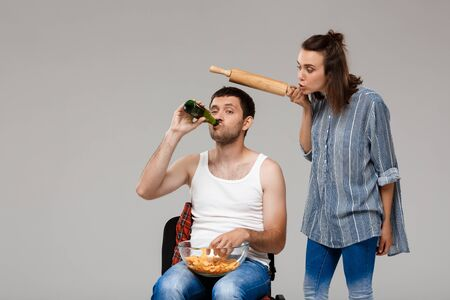 watching football: Young beautiful woman angering with man drinking beer, watching football over grey background. Copy space.