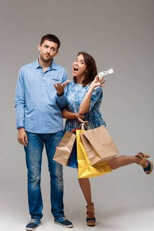 Young woman holding purchases, taking last money from man over grey background. Copy space.