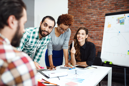 sincere: Colleagues speaking, smiling, discussing new ideas at business meeting. Stock Photo