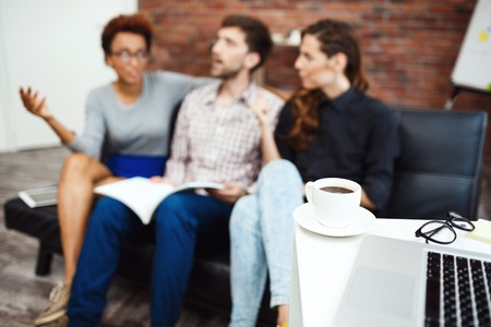 biz: Colleagues communicating during business brake on background. Focus on cup of coffee.