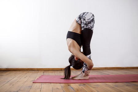 Young beautiful athletic girl practicing indoor yoga asanas on red mat. Wooden floor and white wall background. 免版税图像