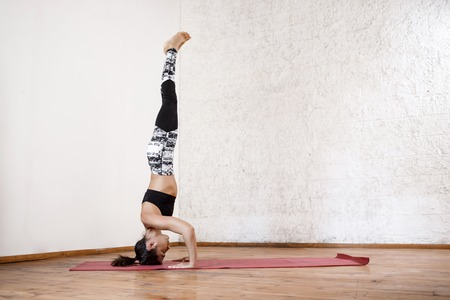 asanas: Young beautiful athletic girl practicing indoor yoga asanas on red mat. Wooden floor and white wall background. Stock Photo