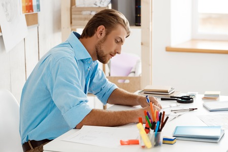 one mature man only: Picture of young handsome confident pensive businessman working sitting at table writing in notebook. White modern office interior background.