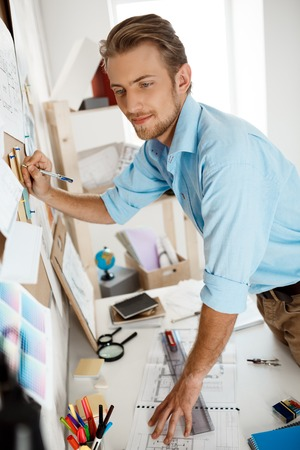 one mature man only: Picture of young handsome businessman standing at table and writing on the paper pinned to corkboard. Office background.