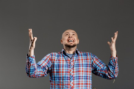 lifting hands: Portrait of handsome middle-aged man screaming up lifting hands in plaid shirt over grey background. Copy space.