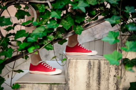pies bonitos: Close up photo of girls legs in red keds going upstairs. Copy space. Foto de archivo