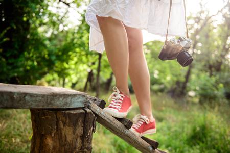 Cierre de la foto de las piernas de la muchacha en keds rojos steping en el escritorio. Espacio de la copia.