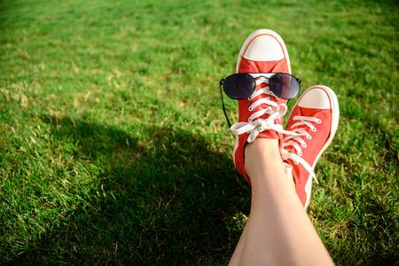 pies bonitos: Ciérrese encima de la foto de las piernas de la muchacha en keds rojos que mienten en hierba. Copie el espacio.