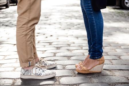 Cierre de la foto de las piernas de par en keds de pie en la calle. Espacio de la copia.