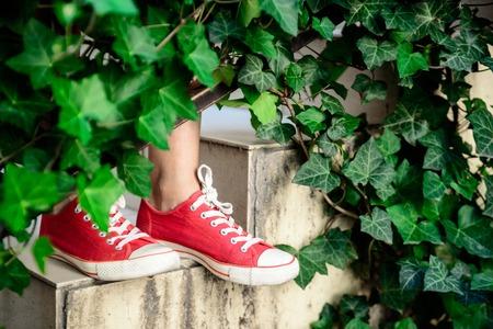 pies bonitos: Ciérrese encima de la foto de las piernas de la muchacha en keds rojos que se colocan en las escaleras. Copie el espacio.
