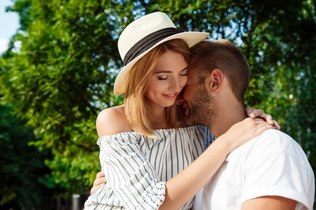 rejoicing: Young beautiful couple smiling, rejoicing, embracing, walking in park Stock Photo