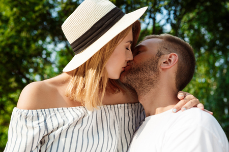 rejoicing: Young beautiful couple smiling, kissing, rejoicing, embracing walking in park