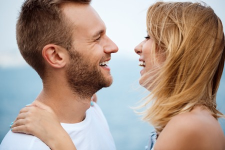 rejoicing: Young beautiful couple smiling, laughing, rejoicing sea background